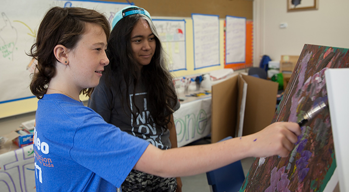 Galileo Summer Quest camper getting art tips from a camp educator.