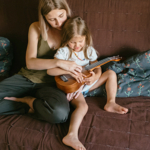 Mom helps daughter play the Ukulele